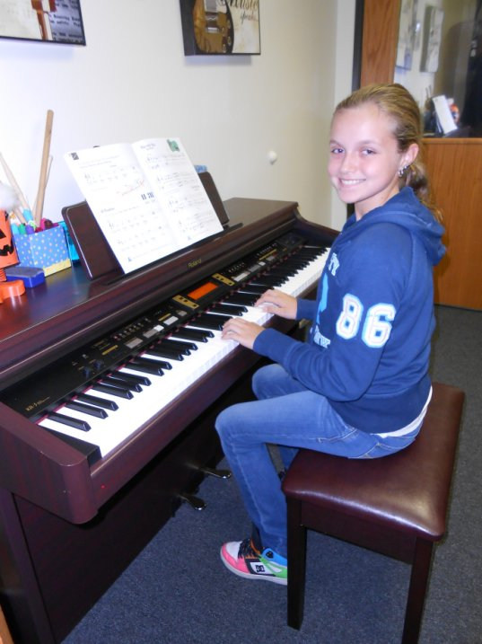 AMA music student Reilly sits at the piano.