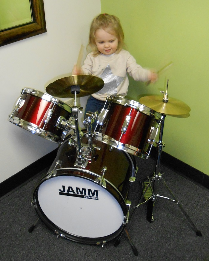 A little girl plays drums
