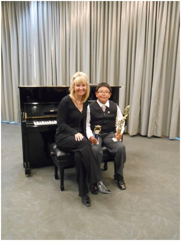 Ann Marie sits at the piano with a student