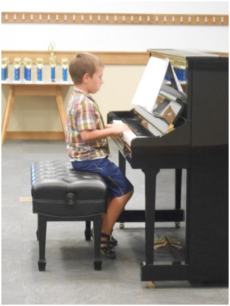 You music student plays the piano at the Spring Recital